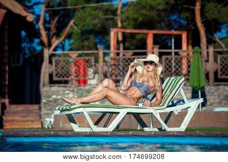 Beautiful girl is sunbathing in swimsuit with pleasure. She is lying near a swimming pool. The lady is enjoying the sun and smiling. She is wearing sunglasses and a hat.