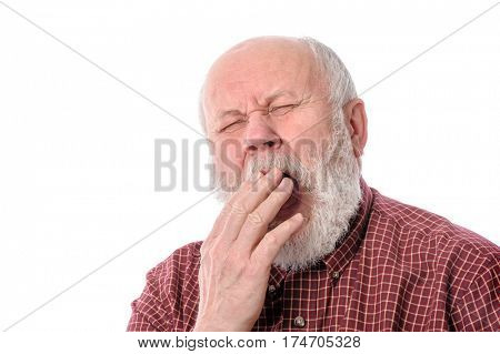 Handsome bald and bearded senior man yawning while covering mouth with hand, isolated on white background