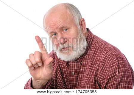 Handsome serious bald and bearded senior man asking to focus the attention, gesturing with his forefinger upwards, isolated on white background