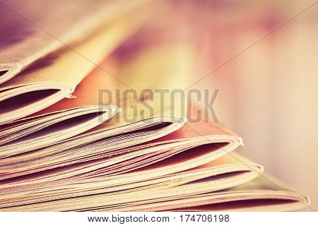 Close up edge of colorful magazine stacking with blurry bookshelf background for bublication and publishing concept extremely DOF with vintage retro color tone