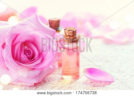 Bottles of Essential Rose Oil for Aromatherapy. Rose Spa concept. Natural pure rose oil or scented water in bottles for spa, skin care or aromatherapy