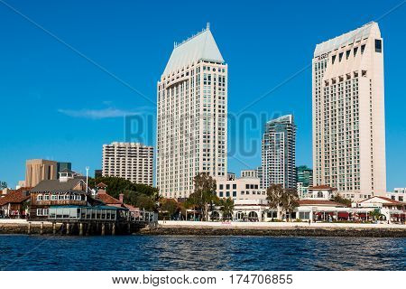 SAN DIEGO, CALIFORNIA - MARCH 2, 2017:  The Seaport Village waterfront shopping and dining complex on San Diego Bay, with adjacent hotels and downtown skyline.