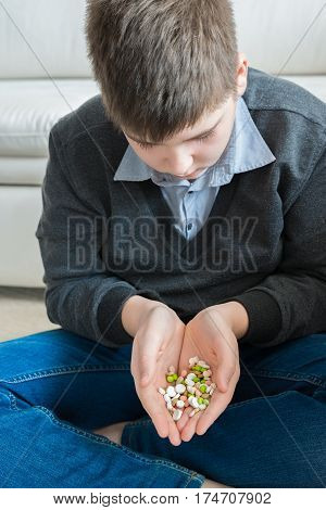 Teenager holding a handful of pills and thinking about a suicide