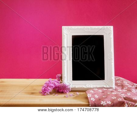 The White vintage photo frame with sweet statice flower with on red pink background and wooden table romance concept