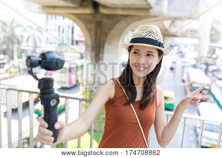 Woman recording video by viedo stabilizer at street of bangkok