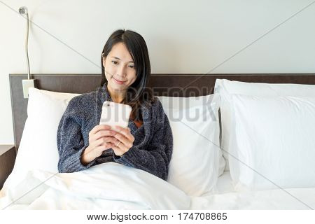 Woman use of cellphone and lay down on bed