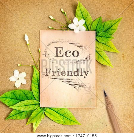 Eco friendly paper sheet with fresh spring green leafs and flower border frame on brown recycle paper background eco natural banner concept