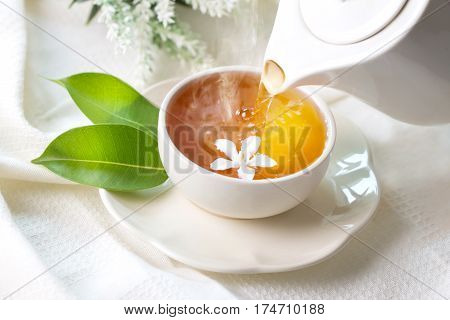 Close up pouring hot jasmine tea in a white tea cup Tea ceremony time concept