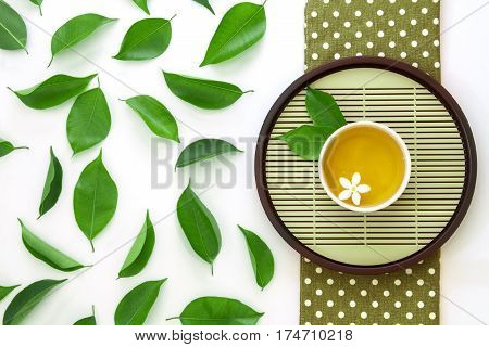 Top view shot of a hot cup of tea with green leaf decoration on white background Organic Tea ceremony time concept