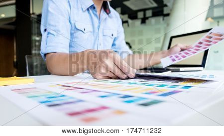 Graphic designer working choosing colour in his office