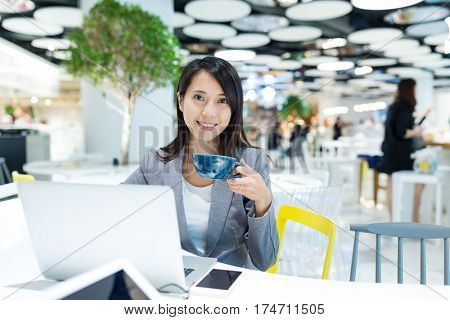 Businesswoman working on laptop computer and drinking of coffee in co-working space