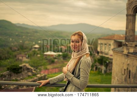Young beautiful girl posing in Gelati monastery mountains in the background