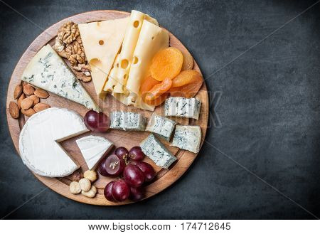 assorted cheeses, nuts and grapes on a black background. vignetting as an artistic effect