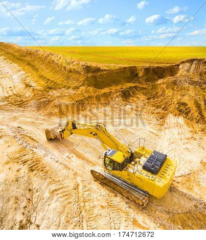 Aerial view of a working excavator in the mine or construction site. Heavy industry from above. Industrial background from devastated landscape.