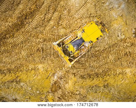 Aerial view of bulldozer on muddy construction site or open cast mine. Heavy industry from above. Industrial background from devastated landscape.