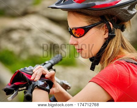 Bicycle teen with ladies bikes in summer park. Bicyclist girl watch on smart watch. Girl looking for road. Smart watch best assistant in travel. Stones on background.
