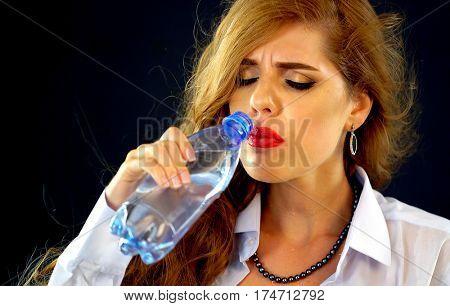 Sensitive teeth woman drinking cold water from bottle . Sudden toothache of thirsty girl in business suit drink . Painful facial expression. Lady with closed eyes and long hair guzzles on black