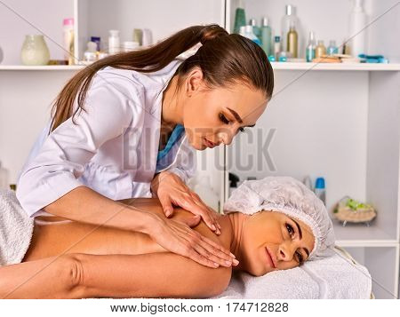 Massage therapy deals. Woman therapist making manual therapy back. Hands of masseuse close up. Treatment of spinal injuries 40 old client in spa salon.  Masseuse use edge of palms.