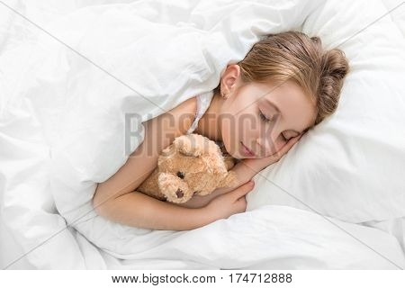 Amazing child napping and hugging her teddy bear in sleep, calm and peaceful