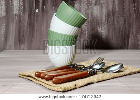 Bowls with wooden silverware on wooden background