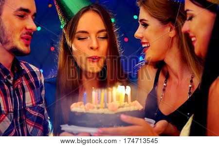 Happy friends birthday celebrating food with celebration cakes. Meet people wear in hat party blow out candles at burning candles. Two women and men have fun in nightclub.