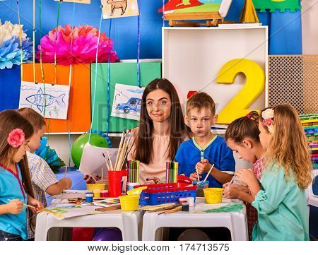 Kids playroom organization of children painting and drawing in kid's club. Craft lesson in primary school. Kindergarten teacher and small students work together. Boys at drawing lesson. Girl paints