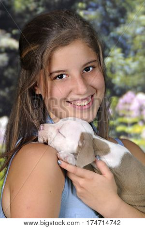 Head and shoulders portrait of a beautiful teen girl delightedly holding her sleeping new puppy on a bright summer day.