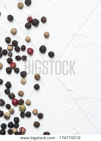 Assorted peppercorns. Medley trio colorful peppercorn on white textured concrete background with copy space. Top view or flat lay. Vertical