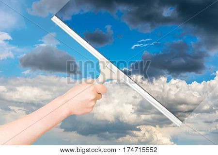Cleaning window with rubber squeegee and cleaning the sky
