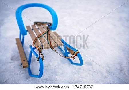 Blue metal and wooden sled on the ground in winter