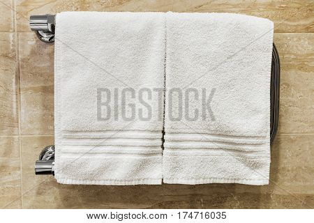 clean towels drying on the heated towel rail