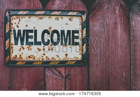 Welcome plaque on a grunge wooden fence background