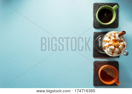 cup of ice cream coffee, tea and cacao at blue paper background