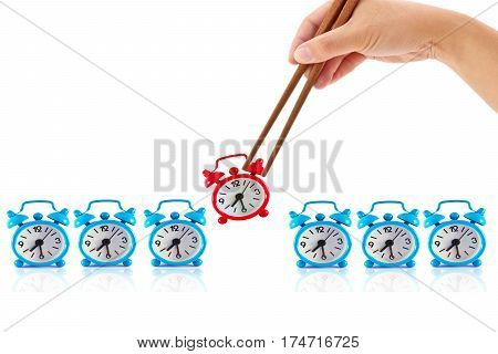 Hand with chopsticks and alarm clock isolated on white