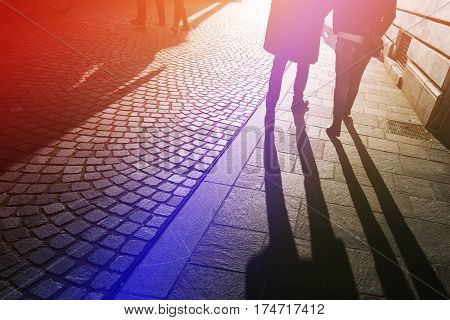 Long shadows of pedestrian people on the street pavement in winter afternoon
