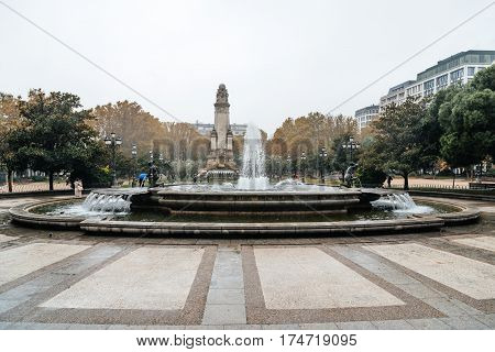 Madrid Spain - November 20 2016: Rainy day in Spain Square of Madrid. Fountain and Cervantes monument on background