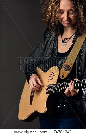 Portrait of young female artist playing solo guitar