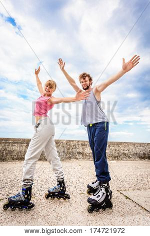 Two People On Rollerblades With Spread Arms.