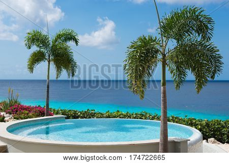 Clear water of round swimming pool and tropical blue ocean palm trees - Curacao, Netherlands Antillen, paradise on the Earth