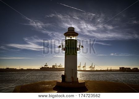 AARHUS DENMARK - NOVEMBER 24 2016: Portside lighthouse in the port of Aarhus. Container Port is the largest in Denmark seen in the background November 24 2016
