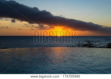 Romantic sunset with round swimming pool and tropical blue ocean palm trees - Curacao - paradise on the Earth