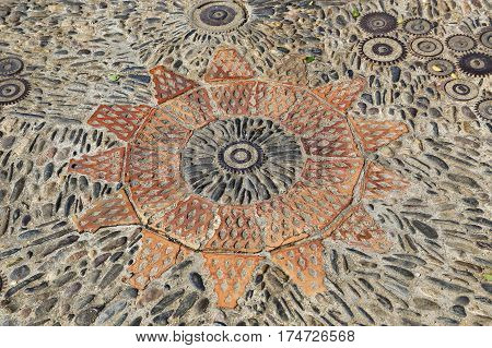 Patterned floor with pattern from pebbles bricks and gears in the park Montjuic Barcelona Catalonia Spain
