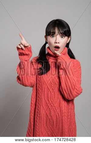 A studio portrait of a twenties Asian woman pointing at something with a finger and looking surprised
