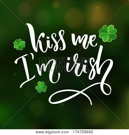 Kiss me, I'm irish. Fun St. Patrick's day quote for t-shirts and cards. Brush lettering design with clovers at green blurred background.