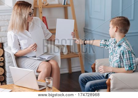 Show it to me. Attractive young woman wearing smart clothes holding two sheets of paper in her hands sitting in semi position