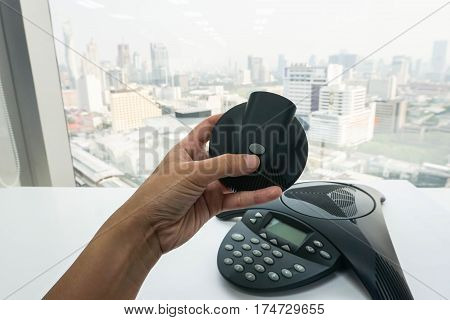 woman hold mobile speaker of conference phone in office