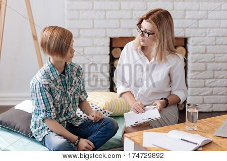 Tell me your problem. Upset boy wearing checked shirt and jeans putting his hands on knees while looking straight