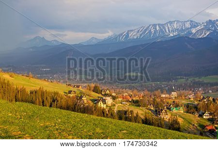 Scenic view of Koscielisko village near Zakopane with panorama of snow caped High Tatras on background Poland in sunlit at spring evening