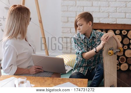 I saw that. Attentive boy wearing casual clothes sitting near female looking on laptop