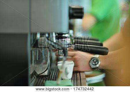 prepares espresso in his coffee shop, close-up.